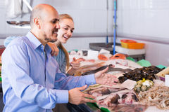 Customers choosing seafood in fish store and smiling Stock Images