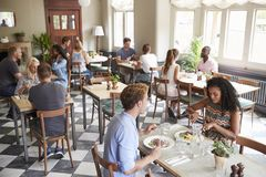 Customers Enjoying Meals In Busy Restaurant royalty free stock images