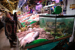 Customers on Fish market. Customers seen next to stands with Fish of different species to be sold exposed on a fish market in the Spanish island of Mallorca royalty free stock image
