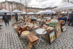 Customers of flea market looking for bargains and antique stuff in mess of vintage decor and retro details. BRUSSELS, BELGIUM - APR 3: Customers of flea market Royalty Free Stock Photography