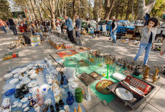 Customers of the flea market making choise in mess of the old kitchen utensils and retro souvenirs Stock Image