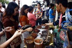Customers line up and buy assorted street food stock photos