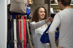 Customers looking at emale handbags in store. Positive customers looking at stylish female handbags in store Stock Photo