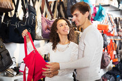Customers looking for handbags. Positive customers looking at stylish female handbags in store royalty free stock photo