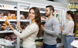 Customers near fridge with meat products Royalty Free Stock Photography