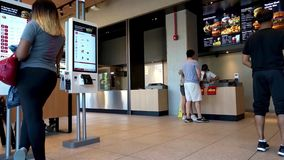 Customers ordering food in McDonald`s. Kiosk and cashier. Hamburger University. West Loop, Chicago - September 15, 2018. Customers place their orders with the stock video
