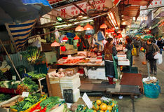 Customers of outdoor market choose seafood, fruits and vegetables on busy narrow street Royalty Free Stock Image