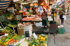 Customers of outdoor market choose seafood, fruits and vegetables on busy narrow street Royalty Free Stock Images