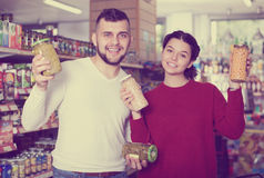 Customers purchasing tinned food at grocery store Stock Photo