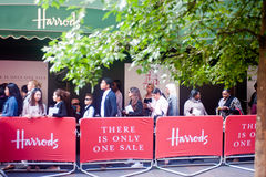 Customers queue outside Harrods in London. London, UK - June 15, 2013: customers queue outside the Harrods store in London on June 15, 2013 for the opening of Stock Photo