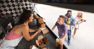 Customers queue and saleswoman at food truck Stock Photos