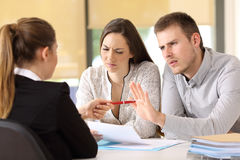 Customers rejecting contract at office. Saleswoman offering a pen to a couple of angry customers that rejects to sing a contract at office royalty free stock photo