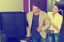 Customers selecting TV set. Happy yoyng customers selecting TV set  in electrical goods store Royalty Free Stock Images