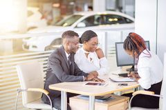 Customers signing some important documents at new car showroom royalty free stock image