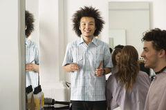 Customers sitting in hair salon, focus on hairdresser holding comb and scissors, smiling portrait Stock Photo