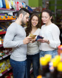 Customers standing near shelves with canned goods at shop. Adult european customers standing near shelves with canned goods at shop Royalty Free Stock Photos