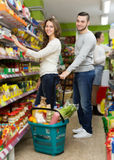 Customers standing near shelves with canned goods at shop. American customers standing near shelves with canned goods at shop Royalty Free Stock Photography