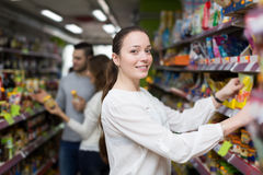 Customers standing near shelves with canned goods at shop Stock Image