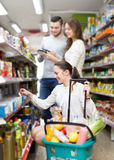 Customers standing near shelves with canned goods at shop Royalty Free Stock Photos
