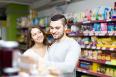 Customers standing near shelves with canned goods at shop Royalty Free Stock Image