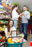 Customers standing near shelves with canned goods at shop Stock Images