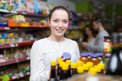Customers standing near shelves with canned goods at shop Stock Photography