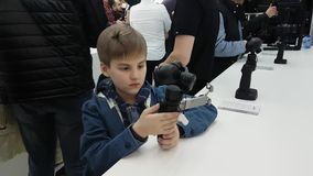 Customers testing Osmo stabilizers at the opening of DJI Store. Moscow, Russia - April 1, 2017: Customers testing Osmo stabilizers at the opening of DJI stock video