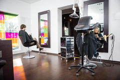 Customers Undergoing Hair Treatment In Beauty Salon Royalty Free Stock Photos
