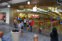 Customers wait outside for The Apple retail store opening as emp. HONOLULU - December 12, 2014: Customers wait outside for The Apple retail store opening as stock photography