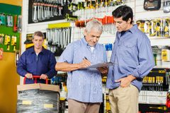 Customers Writing On Checklist In Hardware Store Royalty Free Stock Photography