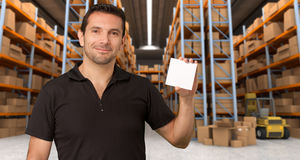 Customizable Message at distribution warehouse. A man holding a blank paper in a distribution warehouse, ideal for inserting your own message stock images