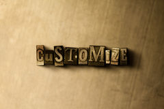 CUSTOMIZE - close-up of grungy vintage typeset word on metal backdrop Stock Photos