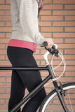 Customized fixie bike and woman over brick wall Royalty Free Stock Image