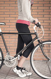 Customized fixie bike and woman over brick wall Stock Photo