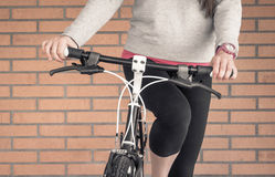 Customized fixie bike and woman over brick wall Stock Image