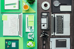 Customized office workspace. Green eco-friendly desktop on one side, standard and monochromatic on the other side Stock Photography