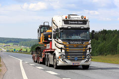 Customized Scania R560 Semi Hauls Excavator along Freeway Stock Photos