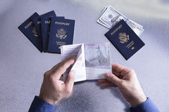 Customs or border official checking a passport. Paging through looking for visas or entry and departure stamps, overhead view of his hands with money for a Royalty Free Stock Image
