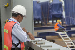 Customs control at work. A customs officer checking the unloading of containers at a commercial harbor Stock Photo
