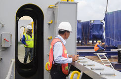 Customs control at work. A customs officer checking the unloading of containers at a commercial harbor Royalty Free Stock Image