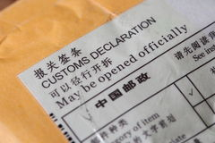 Customs declaration on envelope. Closeup of customs declaration label in English and Chinese on a brown envelope Royalty Free Stock Images