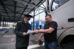 A customs officer reviews the declaration documents for goods transported across the border in front of the weight control point. St. Petersburg, Russia - March royalty free stock images