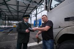 The customs post inspector checks the customs declaration with the driver in front of the weight control point. St. Petersburg, Russia - March 22, 2019: The stock photo