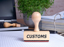 Customs Stamp on desk in the Office. With binder and laptop in the background Royalty Free Stock Photography