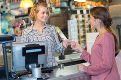 Custormer fêmea usando o terminal do cartão de crédito na verificação geral fotos de stock