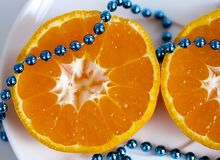 Cut ​​tangerine on a dish with beads royalty free stock photography