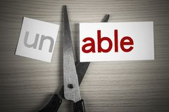 Cut able from unable. A scissor is cuting able from unable on the desk stock photo