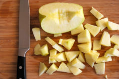 Cut apple. Cutting apples - cut apple and knife on a wooden table Stock Images