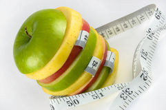 Cut apple with measuring tape Royalty Free Stock Image