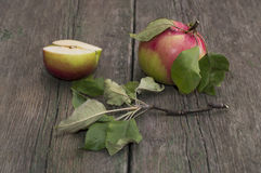 The cut apple and the whole apple with leaves on an old wooden t Stock Image